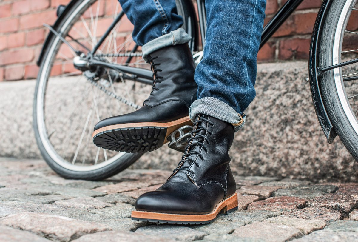 A cropped image of a man wearing Saint Vacant shoes leaning to a bike