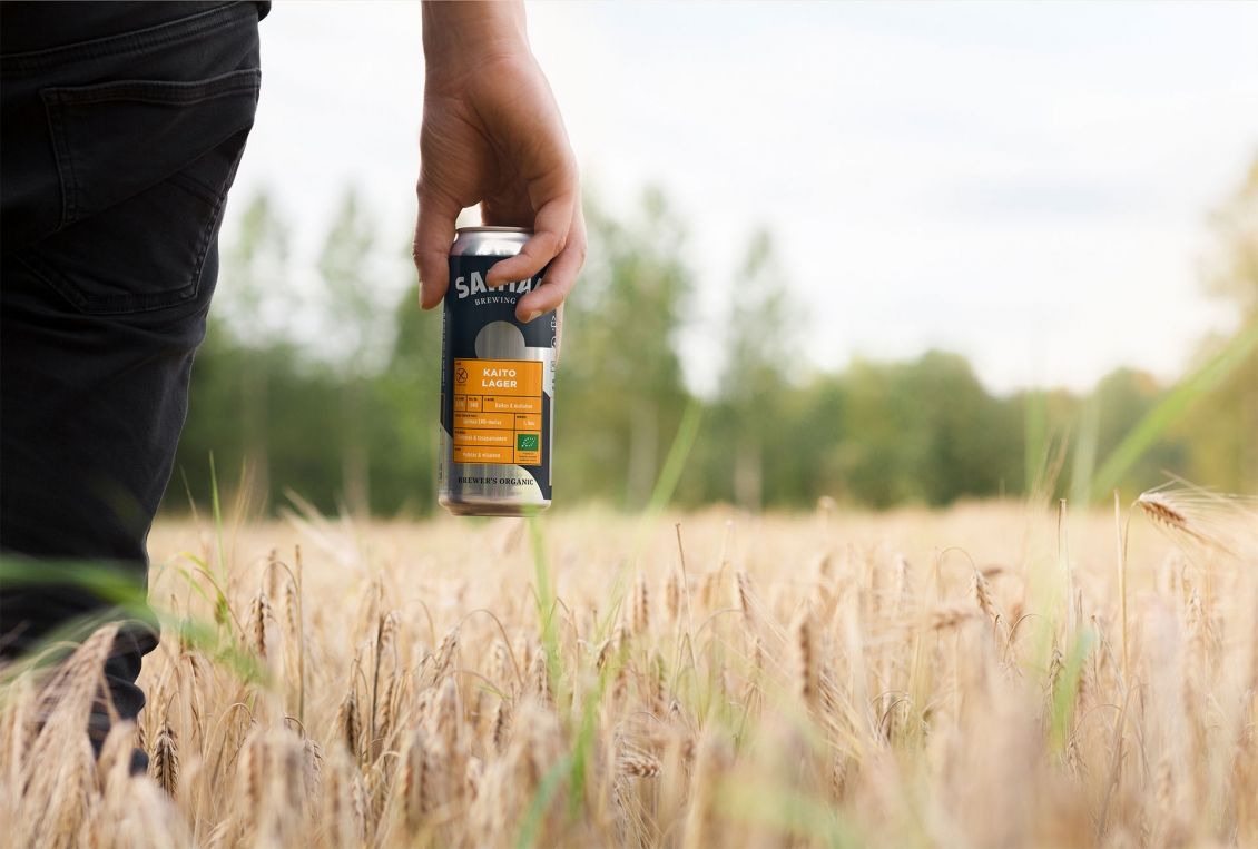 Saimaa Brewing Company brand photography of a man holding a beer in a field by MacWell Creative